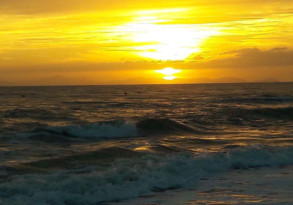 Die Sonne geht über der Insel Elba unter und beleuchtet die Wellen am Strand