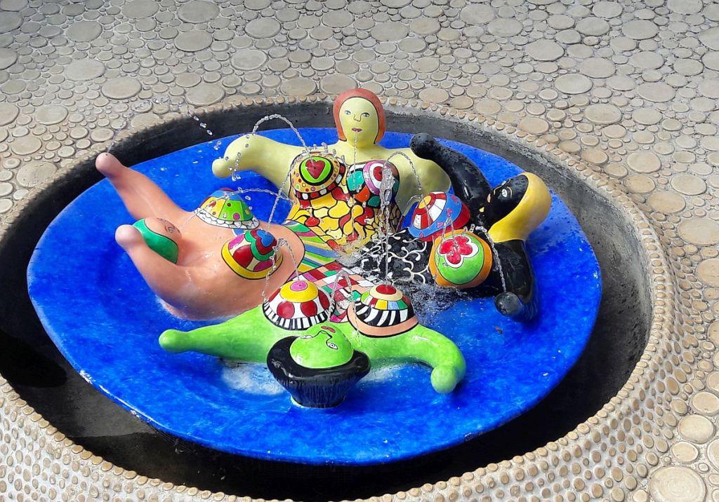 Vier verschieden farbige Frauenfiguren in einem Pool