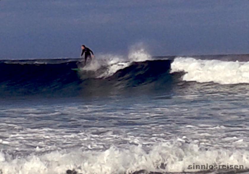 Mann reitet mit Surfbrett auf Welle