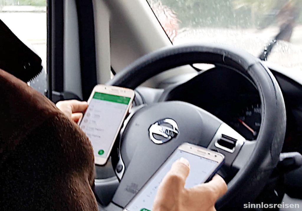 Taxifahrer benutzt zwei Handys während der Fahrt