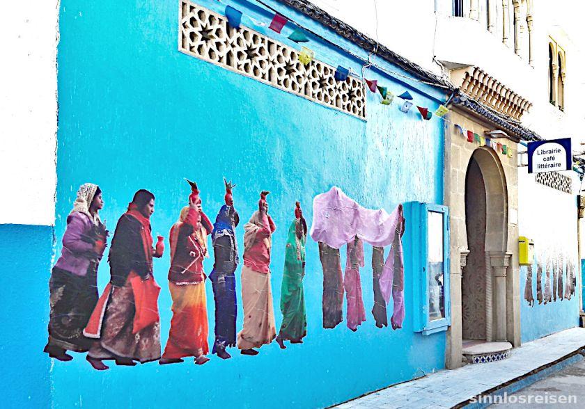Buntgekleidete Frauen auf der Wand einer Bücherei in Marokko